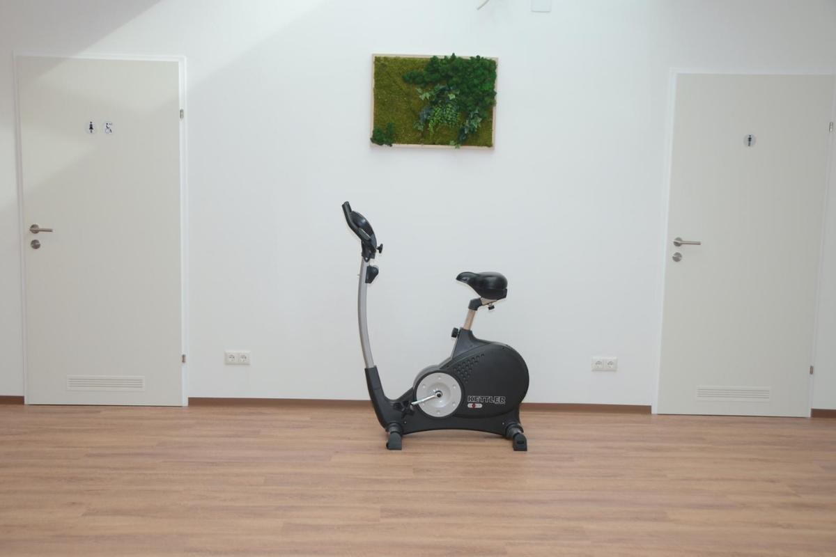 Heller und moderner Warteraum im Therapiezentrum Körperschwung in Taufkirchen an der Trattnach. Es befindet sich hier ein Hometrainer zwischen zwei Toilettenanlagen in der Praxis.