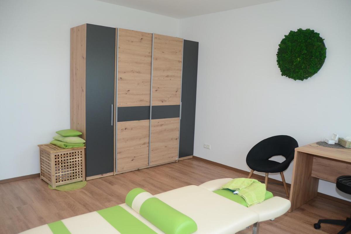 Praxisraum für gewerbliche Massage, Heilmassage & Cranio Sacrale. Es zeigt einen hellen, modernen, gemütlichen, volletablierten Raum mit elektrischer Liege, einem Waschbecken, Schrank und Kommode für genügend Stauraum.