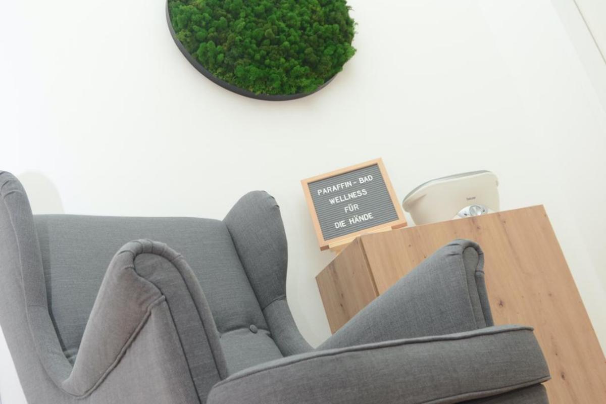 Das Bild zeigt eine gemütliche Atmosphäre im Therapiezentrum Körperschwung in Taufkirchen / Tr. bei einem Paraffinbad. Ein grauer, gemütlicher Ohrensessel, daneben das Paraffinbar und ein grünes, großes Moosbild runden das Bild ab.